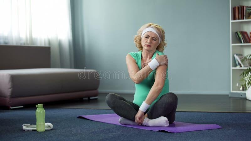 坐瑜伽席子和按摩她的肩膀的运动服的白肤金发的资深妇女 免版税库存照片