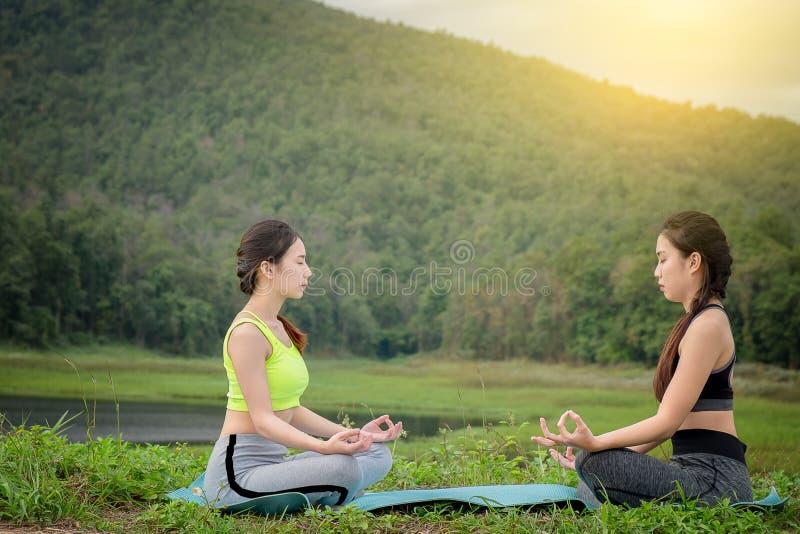坐瑜伽的两个少妇在河附近 健康lif的概念 库存图片