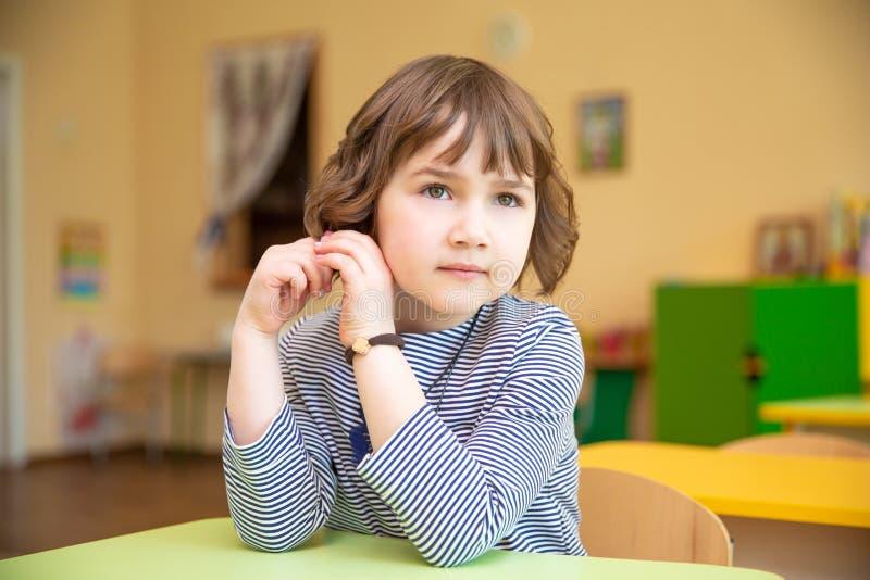 坐用手的逗人喜爱的小女孩画象被扣紧在书桌在教室 免版税库存图片