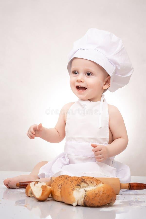 坐用面包大面包的厨师和围裙帽子的迷人的小孩婴孩,愉快地笑 库存照片