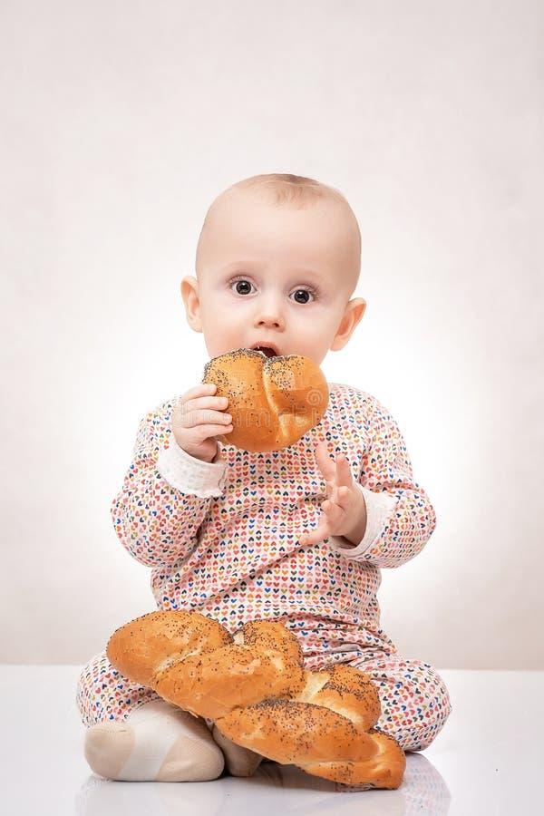 坐用面包大面包的迷人的小孩婴孩,愉快地笑 免版税库存图片