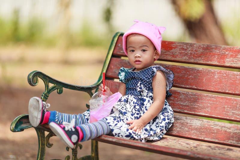 坐用饮料的孤独的亚裔女婴 库存图片