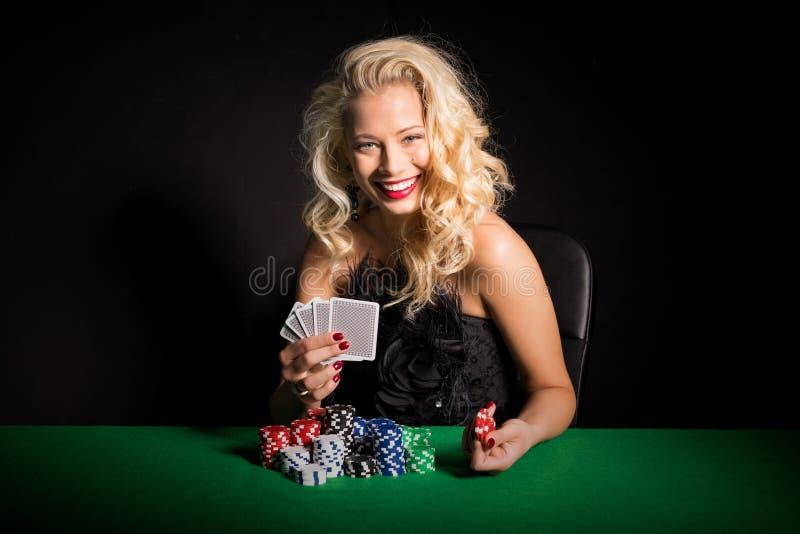 坐由与卡片和芯片的啤牌桌的妇女 免版税库存图片