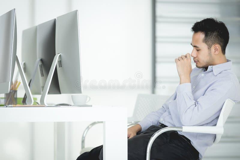 坐由书桌的年轻亚裔商人继续下去工作和休息  免版税图库摄影