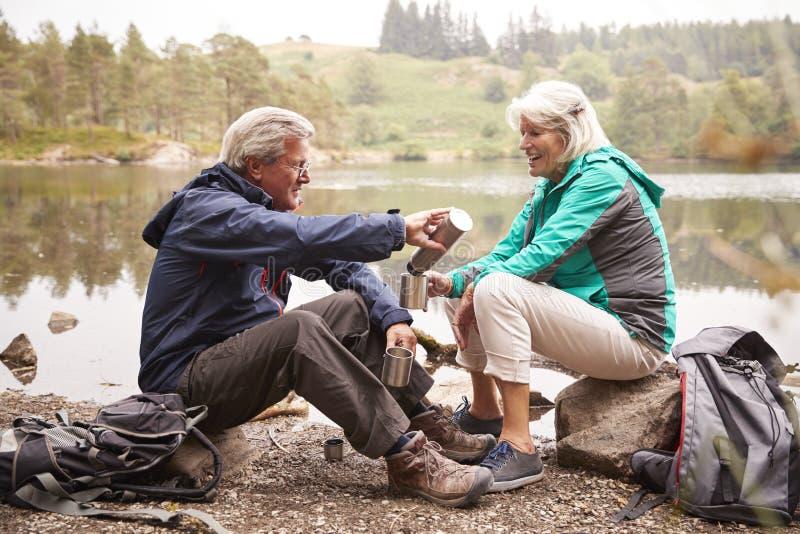 坐由从烧瓶在一个野营假日期间,湖区,英国的一份湖倾吐的咖啡的资深夫妇 库存图片
