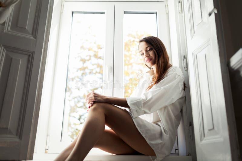 坐由单独窗口的美丽的少妇 免版税库存图片