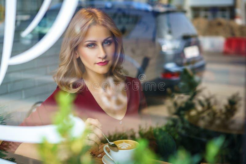 坐由在咖啡馆饮用的咖啡的窗口的美女 免版税库存图片