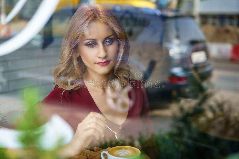 坐由在咖啡馆饮用的咖啡的窗口的美女 图库摄影