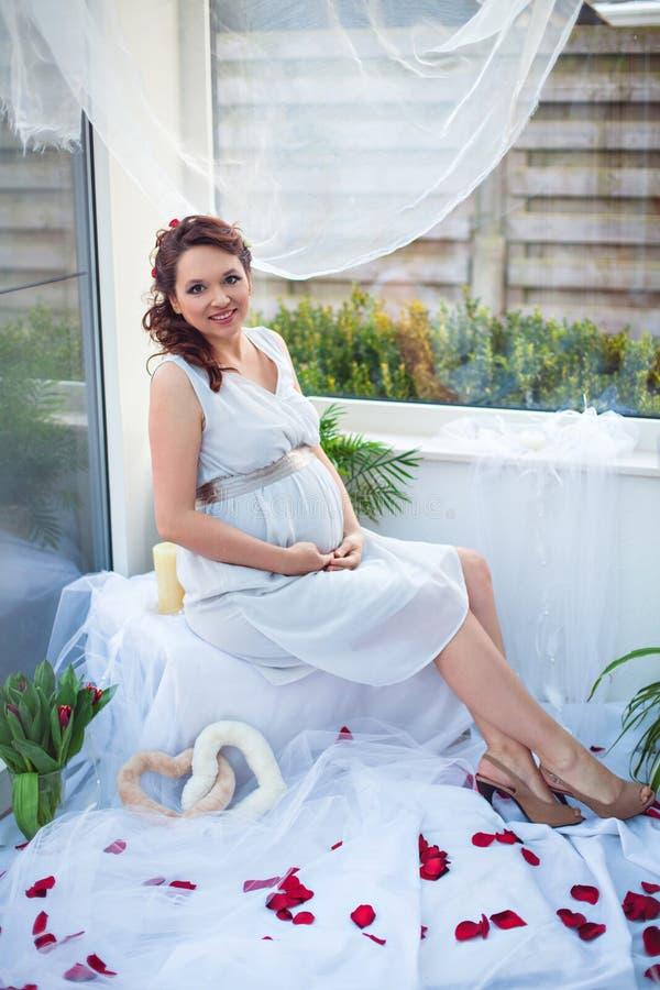 坐由在玫瑰花瓣中的窗口微笑的孕妇 库存照片