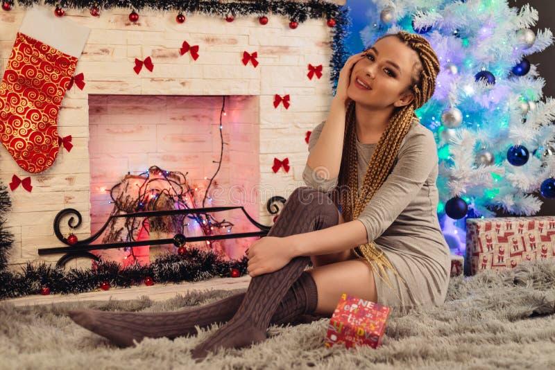 坐由壁炉的少妇 新年` s故事 免版税库存图片