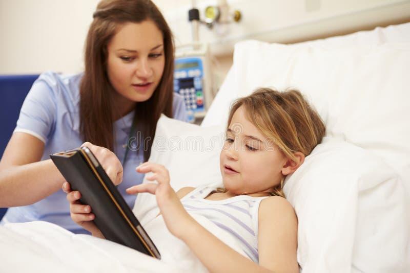 坐由女孩的床的护士在有数字式片剂的医院 免版税库存照片