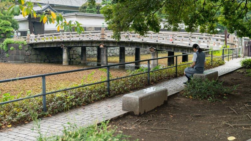 坐由故宫,东京,日本池塘的不明身份的妇女  图库摄影