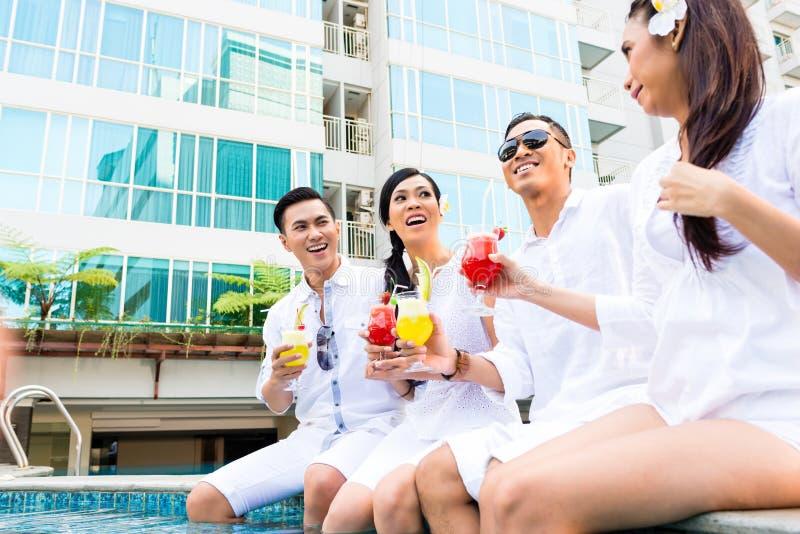 坐由旅馆游泳池的亚裔朋友 免版税库存照片