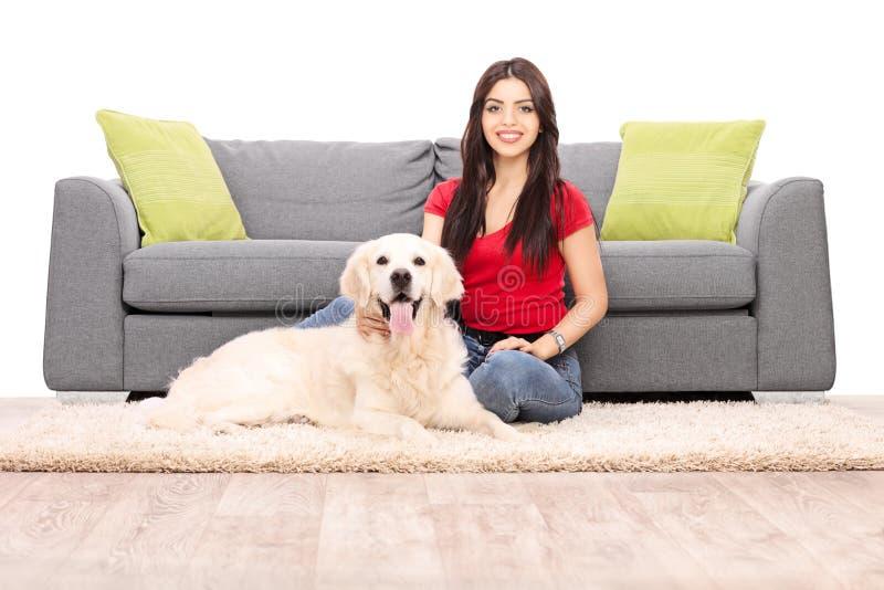 坐由有她的狗的一个沙发的少妇 免版税库存照片