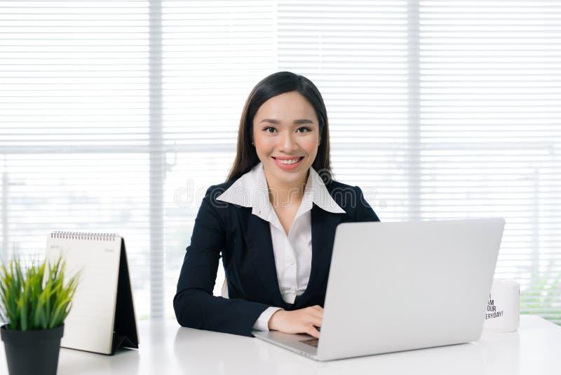 坐由有膝上型计算机的书桌的确信的亚裔女实业家  库存图片