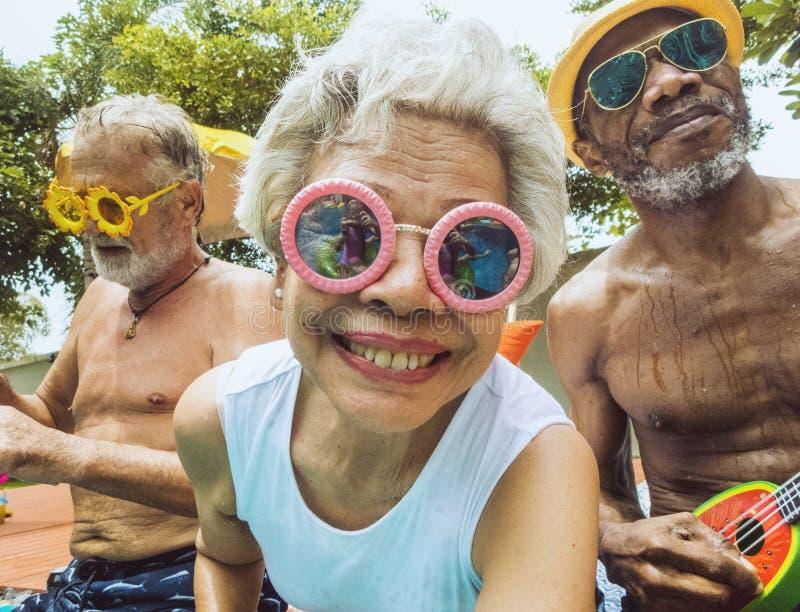 坐由水池的不同的资深成人特写镜头一起享受夏天 免版税库存照片