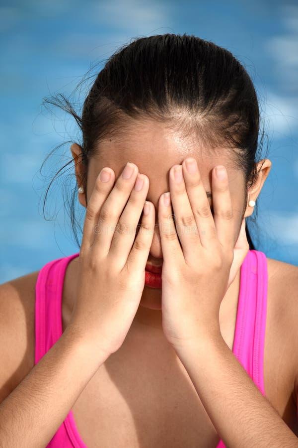 坐由水池的失望的美丽的亚裔青少年的女孩 免版税库存照片