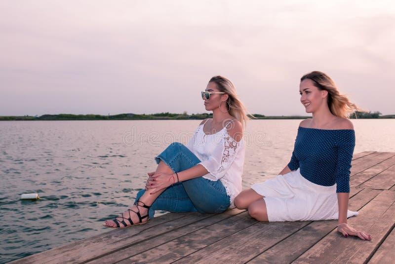 坐由河的美丽的少妇 免版税库存图片