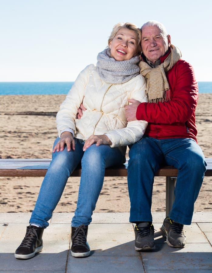 坐由海的成熟夫妇 库存照片