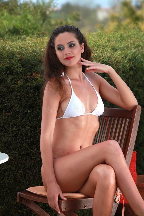 坐由游泳池边的妇女 库存图片
