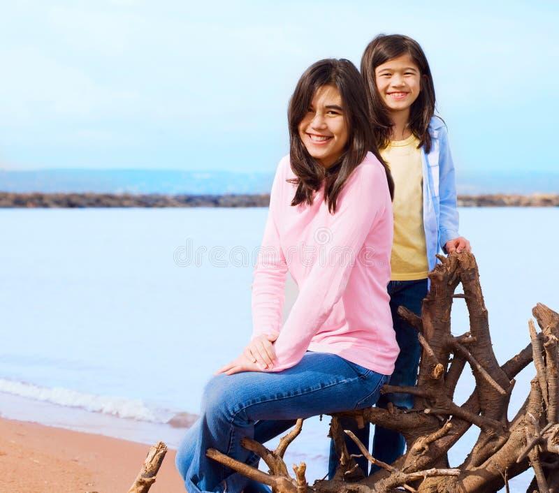 坐由湖岸的两个姐妹在夏天 免版税库存照片
