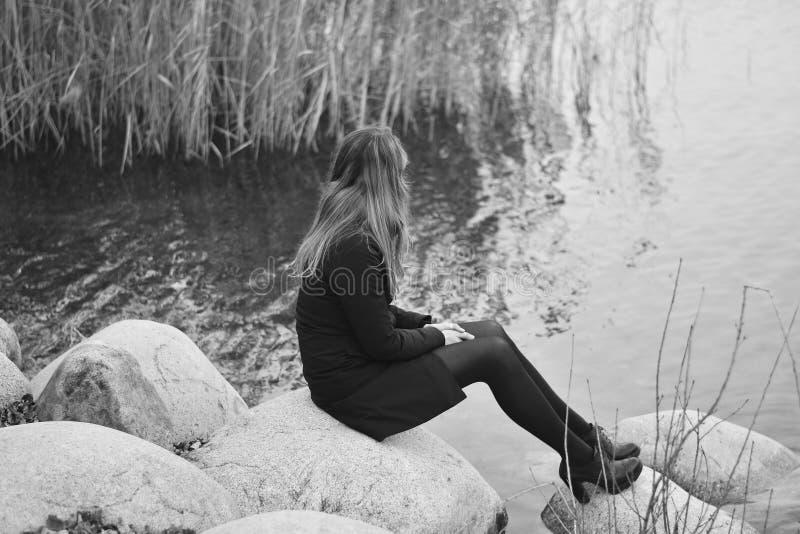 坐由湖的忧郁妇女 图库摄影