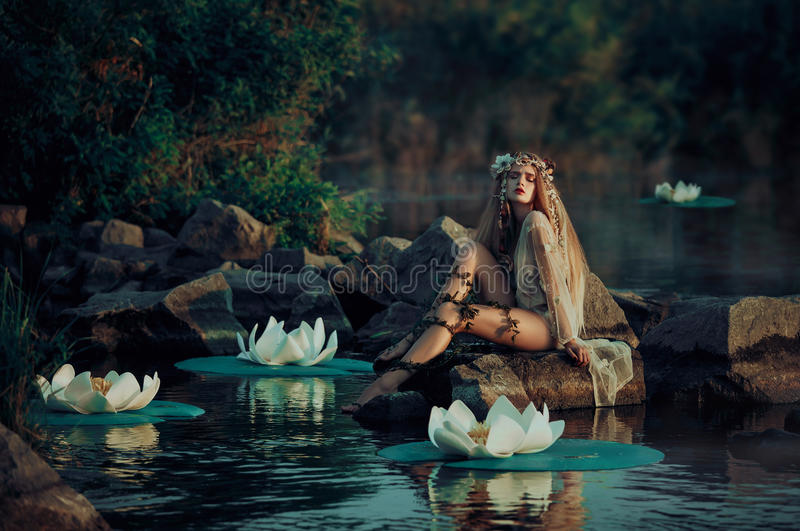 坐由湖的葡萄酒礼服的美丽的妇女 免版税库存图片