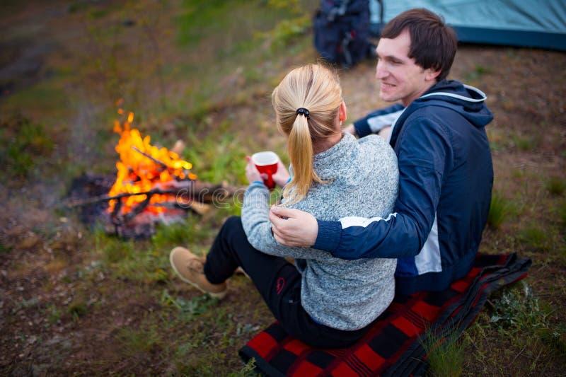 坐由火和饮用的茶的年轻夫妇 免版税库存照片