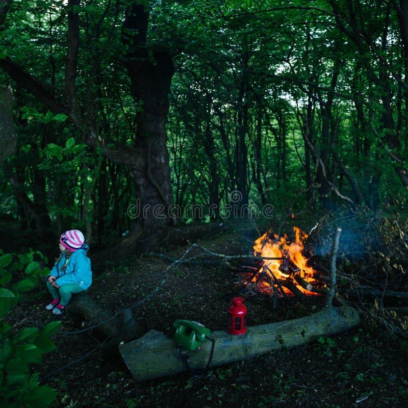 坐由火的一个小女孩在森林里 免版税库存图片