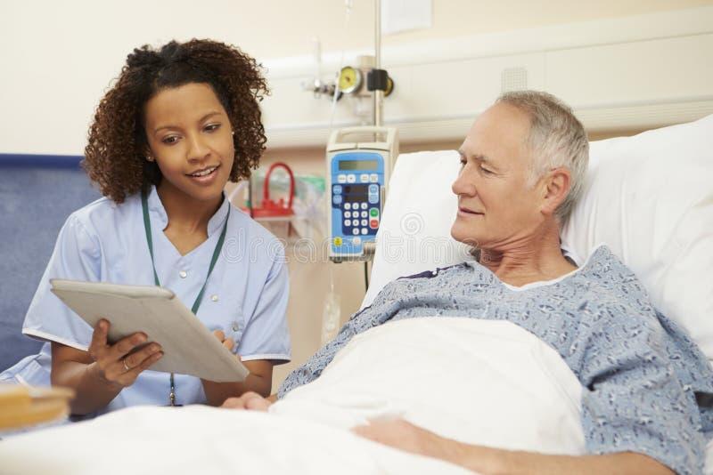 坐由男性患者的床的护士使用数字式片剂 库存图片