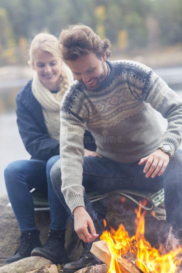 坐由篝火的愉快的夫妇湖岸 库存照片