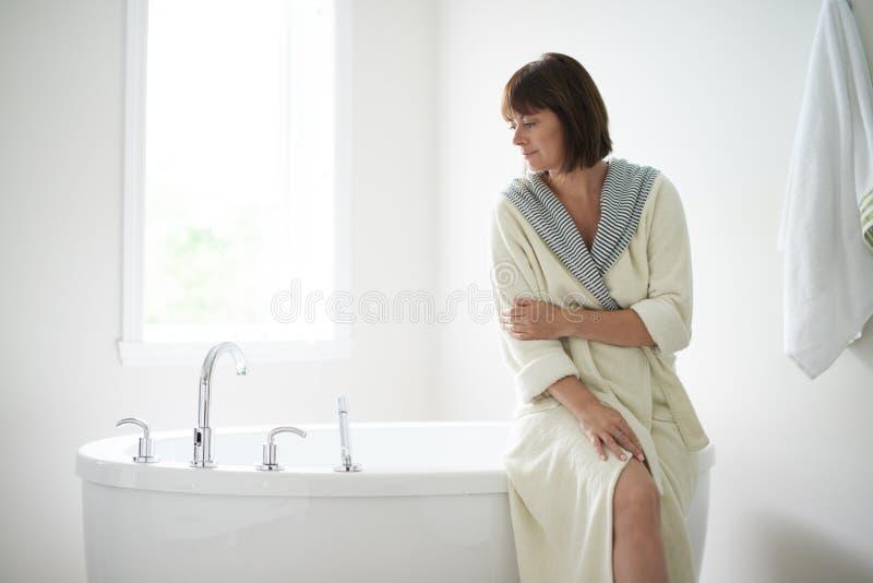 坐由浴缸的平静的成熟妇女 免版税库存图片