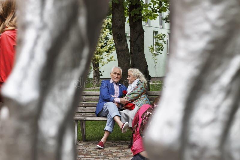 坐的人们,流行的服装,在现代cit的公园长椅 库存照片
