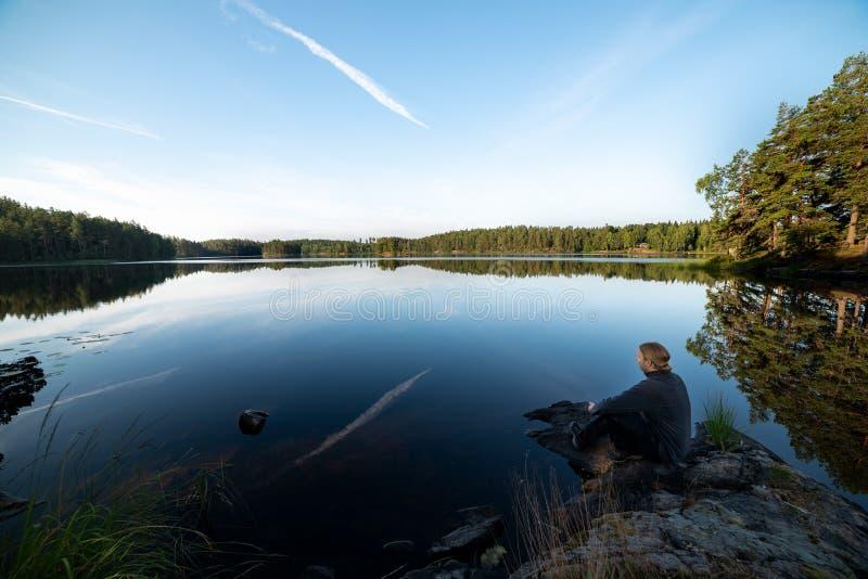 坐的人俯视湖 图库摄影