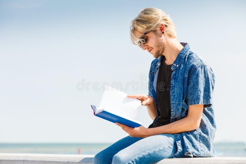 坐的人阅读书外面在晴天 免版税库存照片