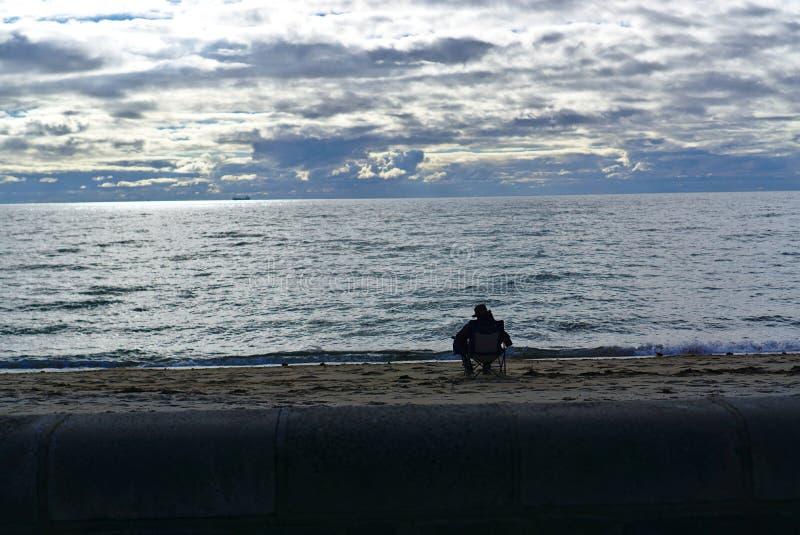 坐的人面对海 免版税库存照片
