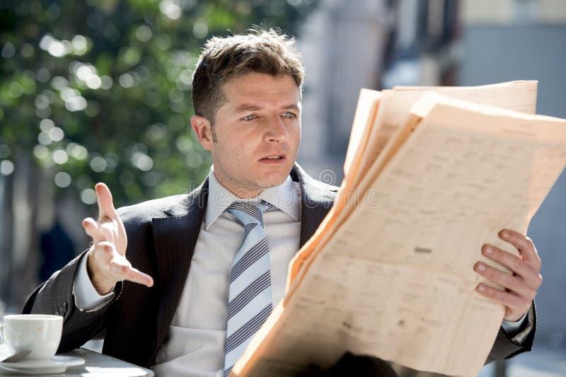 坐的商人户外有早餐清早读书看起来报纸的新闻的咖啡杯生气 免版税库存图片