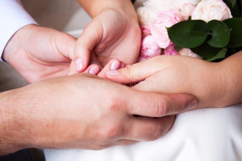 坐的夫妇握有woman&的x27手;在man& x27顶部的s手;s手 库存照片