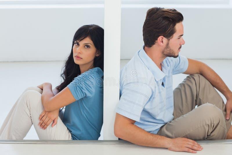 坐的夫妇由墙壁分离 库存照片