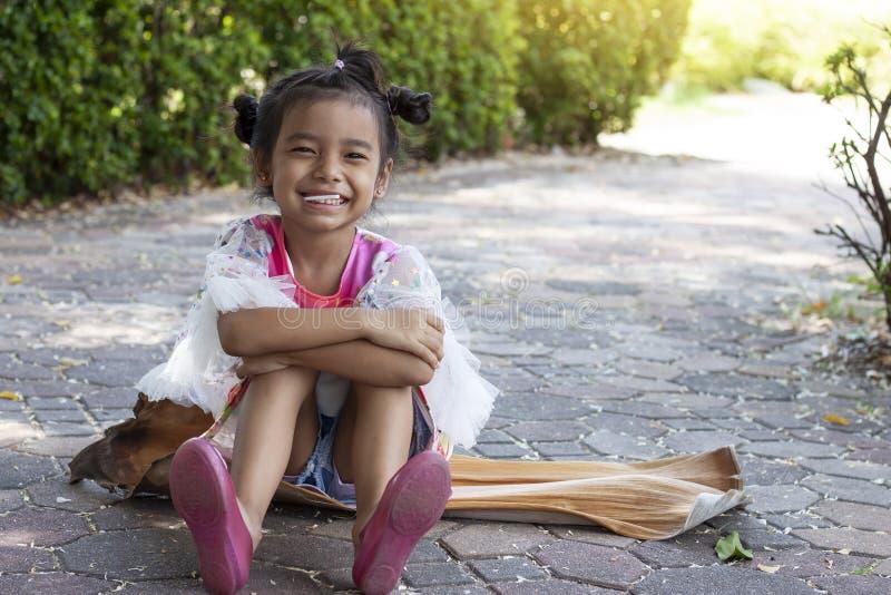 坐的女孩在公园愉快地吃棒棒糖 免版税图库摄影