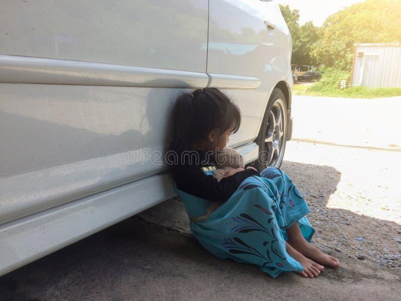 坐的女孩拥抱在汽车旁边的一头熊 免版税库存图片