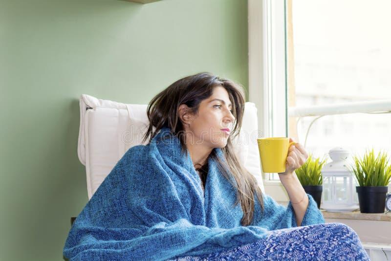 坐的妇女在家,在手中认为用茶 免版税图库摄影
