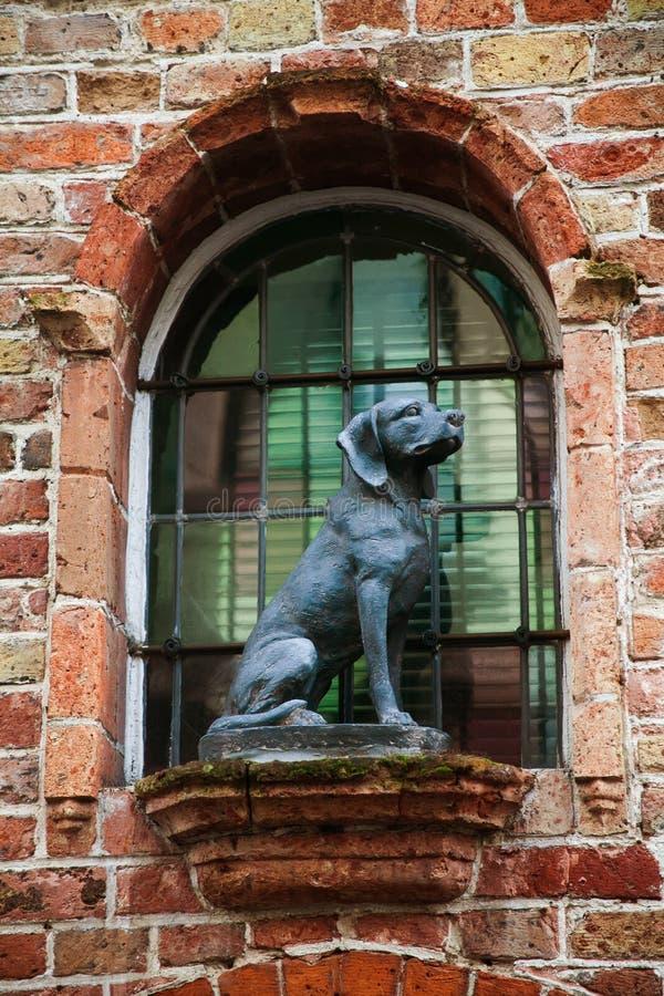 坐的狗雕象纪念碑 葡萄酒红砖墙壁和五颜六色的窗口背景 免版税图库摄影