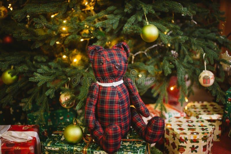坐的玩具熊下用光与礼物盒的圣诞树装饰 免版税图库摄影