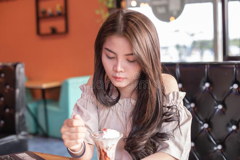 坐的美女吃冰淇淋在商店 免版税库存照片