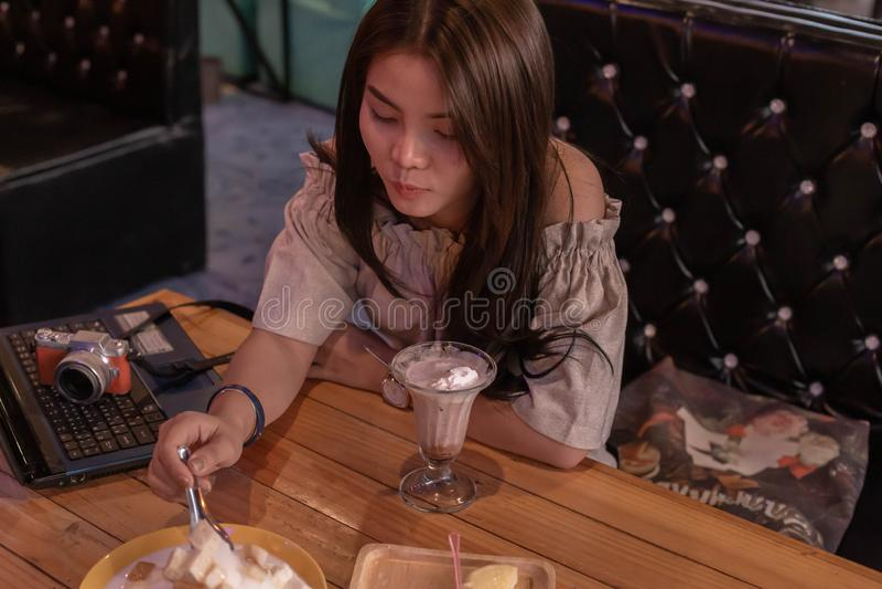 坐的美女吃冰淇淋在商店 免版税库存图片