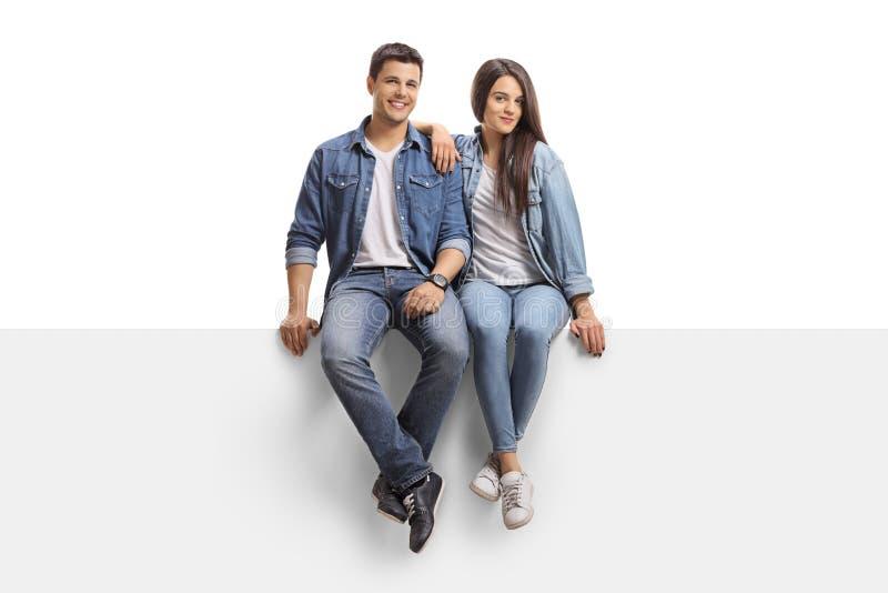 坐盘区和看照相机的年轻夫妇 免版税库存图片