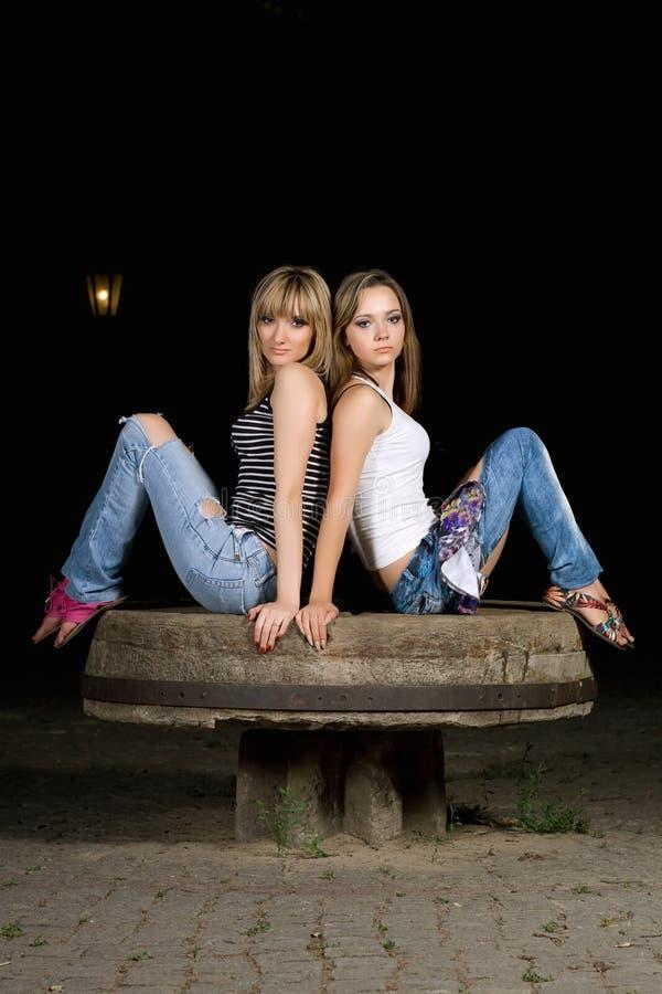 坐石头二的可爱的女孩 免版税库存照片