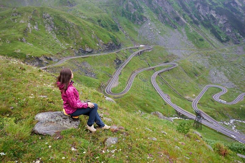坐石头享受美妙的山风景的女孩 Transfagarashan高速公路 库存照片