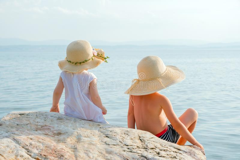 坐石头和看对海洋的后面观点的两个孩子 一点在海洋附近的旅客 男孩和女孩在夏天 免版税库存照片